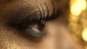 Vrouwelijk het knipperen oog van de Afrikaanse vrouw omvat met gouden oogschaduw en eyeliner De mening van de close-up Samenstell stock videobeelden