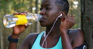 Vrouwelijk jogger drinkwater in bos4k stock videobeelden
