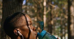 Vrouwelijk jogger drinkwater in bos4k stock video