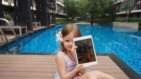 Vrouwelijk jong geitje die selfie op tablet tonen en dichtbij zwembad zitten stock videobeelden