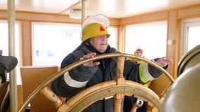 Vrouwelijk kapitein het draaien stuurwiel in navigatiebrug bij drijvend schip De leidingsroer van de vrouwenzeeman van varende bo stock video