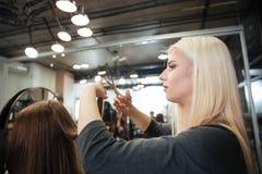 Vrouwelijk kapper scherp haar van vrouwencliënt bij schoonheidssalon stock afbeelding