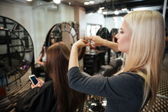 Vrouwelijk kapper scherp haar van vrouwencliënt bij schoonheidssalon stock fotografie