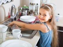Vrouwelijk kind die dishware thuis schoonmaken Royalty-vrije Stock Afbeelding