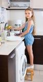 Vrouwelijk kind die dishware thuis schoonmaken Stock Foto's