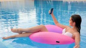 Vrouwelijk maakt foto op androïde en zwemmen op Opblaasbare ring in Zwembad stock video