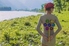 Vrouwelijk model met stuk speelgoed erachter windmolen royalty-vrije stock fotografie