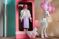 vrouwelijk model in roze pruik die zich in decoratieve doos bevinden stock fotografie