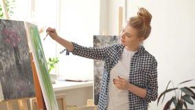 Vrouwelijk mooi kunstenaar het schilderen beeld, die spatel in workshop gebruiken stock video