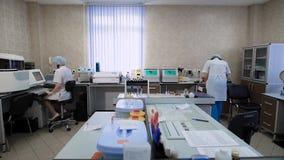 Vrouwelijk onderzoek twee die assistans in laboratorium werken Verpleegsterszitting op de stoel die nota's over computermonitor m stock footage