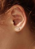 Vrouwelijk oor met diamantoorringen royalty-vrije stock foto