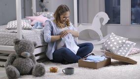 Vrouwelijk openingsleveringspakket met babykleren stock videobeelden