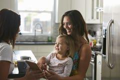 Vrouwelijk paar die in de keuken met hun dochter spreken stock fotografie