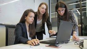Vrouwelijk personeel die terwijl het bekijken PC-het scherm in groot bedrijf spreken stock video