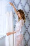 Vrouwelijk portret van leuke dame in witte robe binnen Stock Foto's