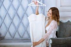 Vrouwelijk portret van leuke dame in witte robe binnen Royalty-vrije Stock Afbeeldingen