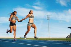 Vrouwelijk relais rennend team op renbaan royalty-vrije stock foto's