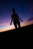 Vrouwelijk silhouet bij zonsondergang Royalty-vrije Stock Foto's