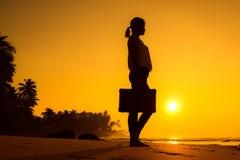 Vrouwelijk Silhouet die langs Oceaankust met Bagagezak enj blijven Stock Fotografie