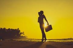 Vrouwelijk Silhouet die langs Oceaankust met Bagagezak enj blijven Royalty-vrije Stock Foto's