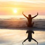 Vrouwelijk silhouet die yogaoefening doen bij mooie zonsondergang op het overzeese strand Stock Foto's