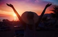 Vrouwelijk silhouet op tropisch strand bij zonsondergang Stock Foto