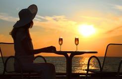 Vrouwelijk silhouet op zonsondergang achter lijst Royalty-vrije Stock Fotografie