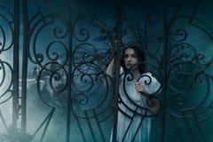 Vrouwelijk slachtoffer bij de poorten van de oude begraafplaats stock afbeeldingen