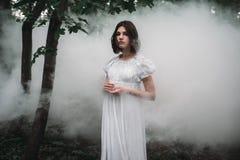 Vrouwelijk slachtoffer in witte kleding in het nevelige bos stock afbeeldingen