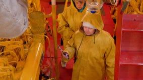 Vrouwelijk team van werktuigkundigen die aan motorcompartiment bij varend schip werken Reparatie en onderhoud van industrieel sch stock footage