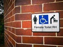 Vrouwelijk Toegankelijk Toilet links & Babyverandering, Gehandicapt Toegankelijk Teken op de rode bakstenen muur stock foto