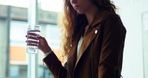Vrouwelijk uitvoerend drinkwater bij haar bureau stock video