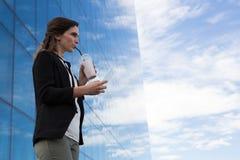 Vrouwelijk uitvoerend gebruikend glasblad terwijl het hebben van milkshake royalty-vrije stock afbeeldingen