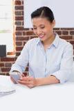 Vrouwelijk uitvoerend tekstoverseinen in bureau royalty-vrije stock fotografie