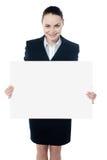 Vrouwelijk uitvoerend tonend leeg aanplakbord aan camera stock foto