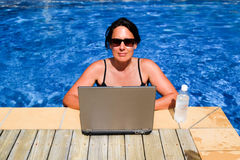 Vrouwelijk uitvoerend werkverslaafde die aan laptop computer in swimmi werken Royalty-vrije Stock Afbeeldingen