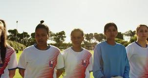 Vrouwelijk voetbalteam dat zich naast elkaar op voetbalgebied bevindt 4K stock video