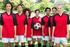 Vrouwelijk voetbalteam met bal bij park royalty-vrije stock foto