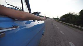 Vrouwelijk wapen buiten het retro auto spelen met wind tijdens de zomerreis Het jonge vrouw golven met haar dient wind bij reis i stock video
