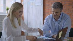 Vrouwelijke accountant die met een cliënt in het bureau werken demonstratie van grafieken en rapporten over de computer 4K stock video