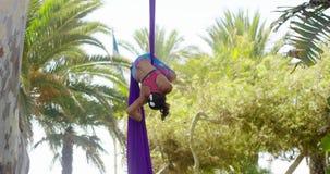 Vrouwelijke acrobaat die in openlucht aan zijdelinten werken stock video