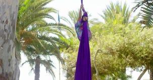 Vrouwelijke acrobaat die in openlucht aan zijdelinten werken stock footage