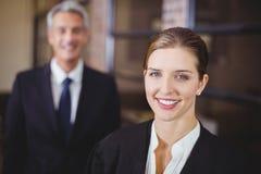 Vrouwelijke advocaat die terwijl mannelijke collega op achtergrond glimlachen royalty-vrije stock foto
