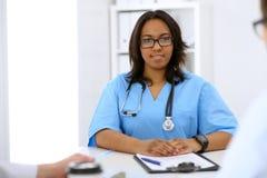 Vrouwelijke Afrikaanse Amerikaanse medische arts met collega's op achtergrond bij het ziekenhuis Geneeskunde en gezondheidszorgco royalty-vrije stock foto