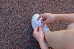 Vrouwelijke agent die haar sportschoen binden Stock Afbeeldingen