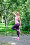 Vrouwelijke agent die met mooi cijfer uitrekkende oefening doen stock fotografie