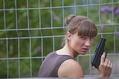 Vrouwelijke agent met kanon het verbergen Royalty-vrije Stock Afbeelding