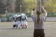 Vrouwelijke Amerikaanse voetbalscheidsrechter en vage spelers in de rug stock fotografie
