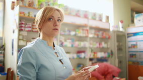 Vrouwelijke apotheker die zich bij teller in apotheek bevinden stock videobeelden
