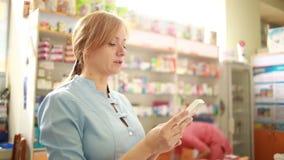 Vrouwelijke apotheker die zich bij teller in apotheek bevinden stock footage